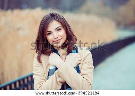 Woman having cold. Closeup portrait headshot professional beautiful confident young girl holding hugging herself isolated park cityscape outdoor background. Multicultural mixt race asian russian model - stock photo