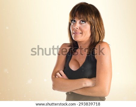 Woman having doubts over ocher background - stock photo