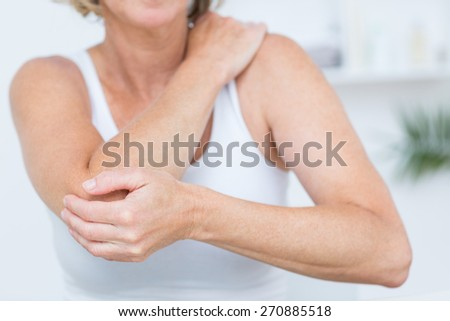 Woman having elbow pain in medical office - stock photo
