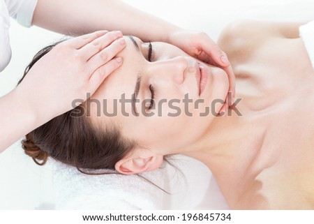 Woman having face massage on isolated background