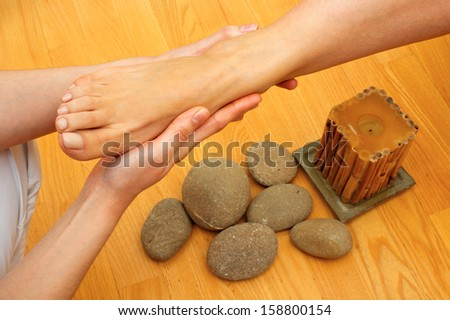 woman having foot massage in spa salon by masseur - stock photo