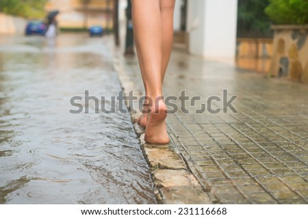 Woman having fun on the street after the rain. - stock photo