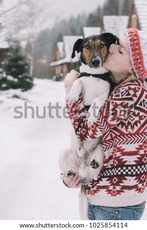 Woman having fun with her terrier on winter vacation