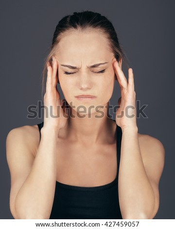 Woman having headache on gray background