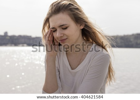 Woman having headache on lake background