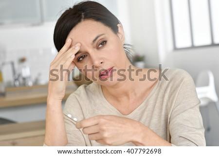 Woman having headache, taking pills - stock photo