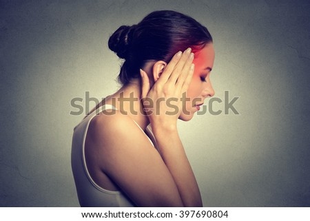 Woman having headache with her head in her hands isolated on gray wall background - stock photo