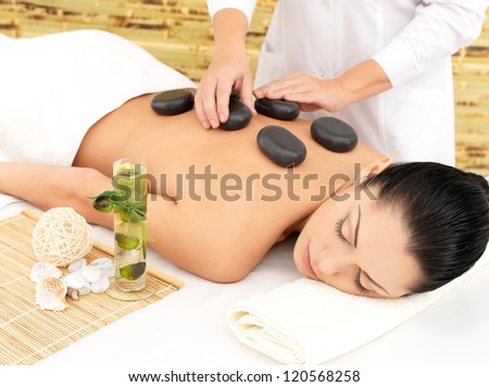 Woman having hot stone spa  massage of back in beauty salon - stock photo