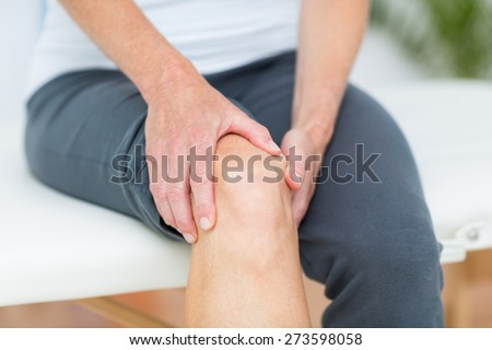 Woman having knee pain in medical office - stock photo