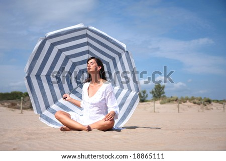 woman having recreatin under blue white striped parasol on the coast - stock photo