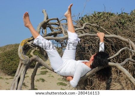 woman having rest on a tree branch