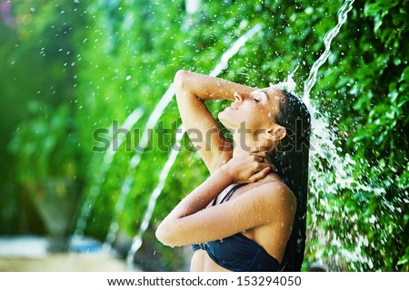 woman having shower under tropical waterfall, bali - stock photo