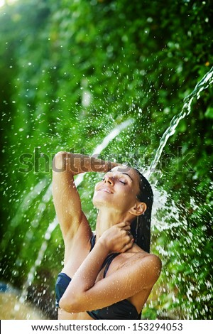 woman having shower under tropical waterfall, bali