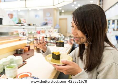 Woman having sushi in restaurant - stock photo