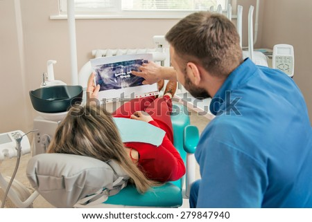 Woman having teeth examined at dentist. Dentist showing patient his X-ray teeth image - stock photo