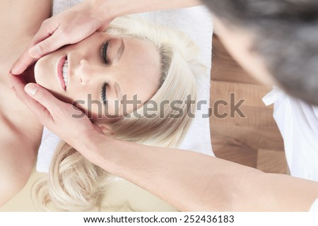 Woman having therapy massage of back in the spa salon. Beauty treatment concept. Blonde young woman relaxing with hand massage at beauty spa. Lumbar massage. Studio shot. White background.
