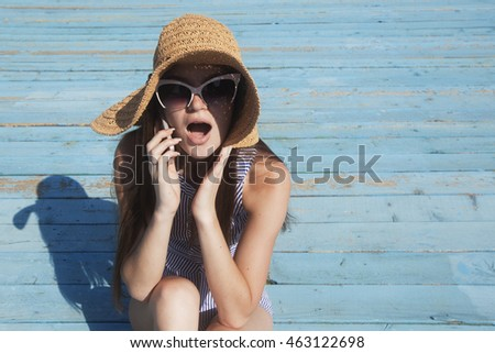 Woman heads the shocking news by the phone on the vacation on the beach