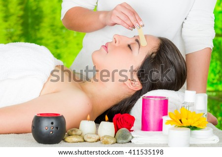 Woman headshot profile, lying with eyes closed and hand applying wax to eyebrow using wooden stick