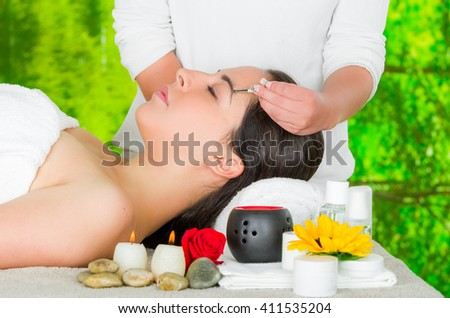 Woman headshot profile,lying with eyes closed and hand holding tweezer pulling eyebrow hairs