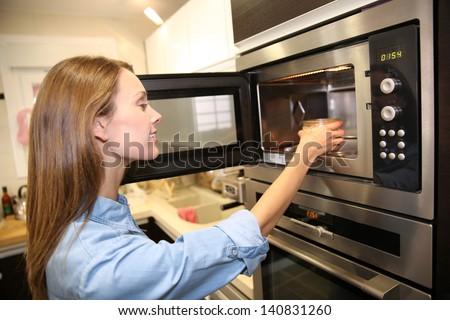 Woman heating dish in microwave - stock photo