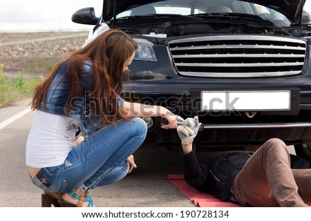 Woman helping a mechanic fix her car kneeling down in the road handing him his equipment as he works under the engine compartment - stock photo