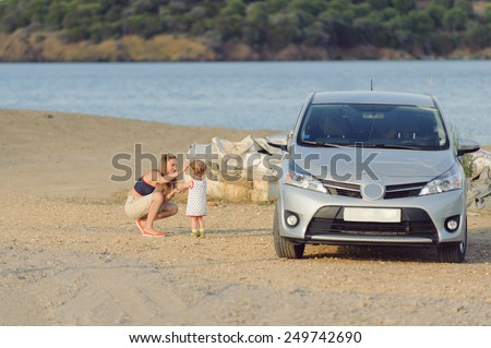 woman helping child to put on sunglasses on river's shore - stock photo