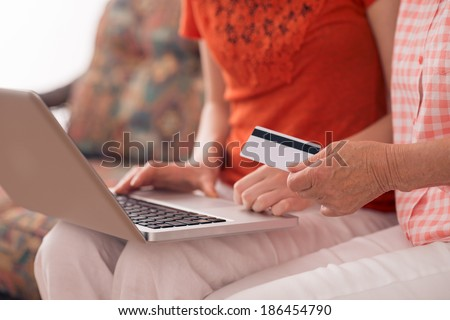 Woman helping her grandmother to make purchases on the internet - stock photo