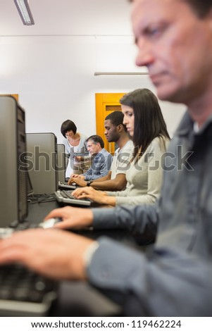 Woman helping her student with the computer in computer class - stock photo