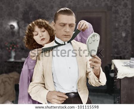 Woman helping man tie bow tie - stock photo