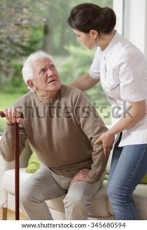 Woman helping old man to stand up - stock photo