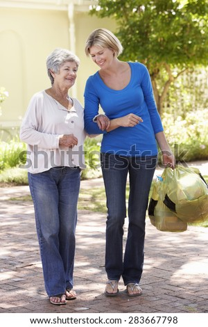 Woman Helping Senior Female With Shopping - stock photo