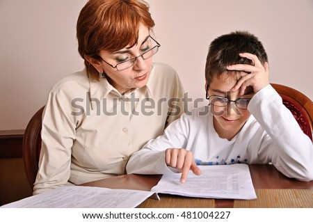 Woman helping young schoolboy to do his homework. Selective focus.