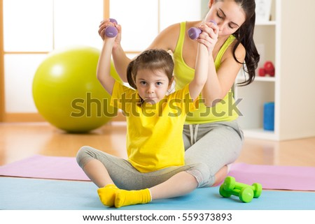 Woman helps little child doing fitness exercises with dumbbells in gym