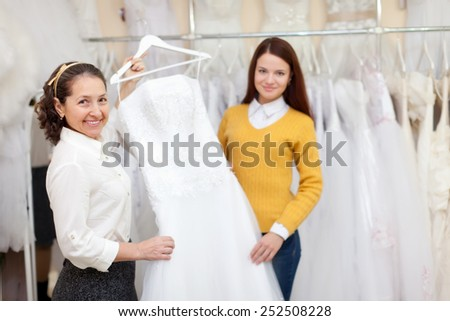 Woman helps the bride in choosing bridal gown at shop of wedding fashion. Focus on mature - stock photo