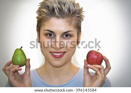 woman hesitating : holding a pear and  an apple - stock photo