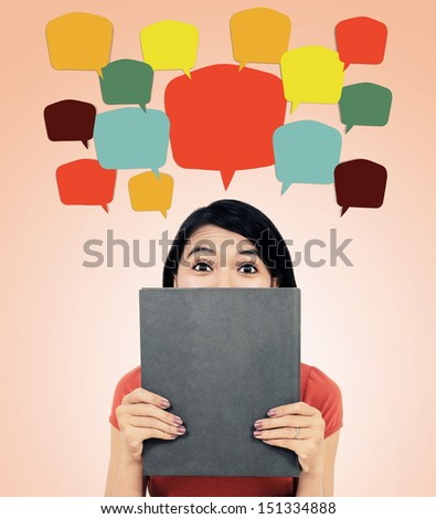 woman hiding behind a book with colorful text balloons, isolated on white background - stock photo