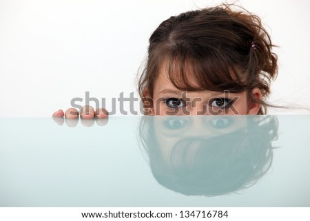 woman hiding behind a glass table