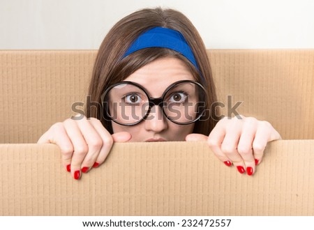 Woman hiding behind a moving box