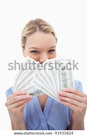 Woman hiding behind bank notes against a white background