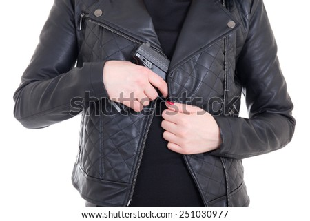 woman hiding gun in leather jacket isolated on white background