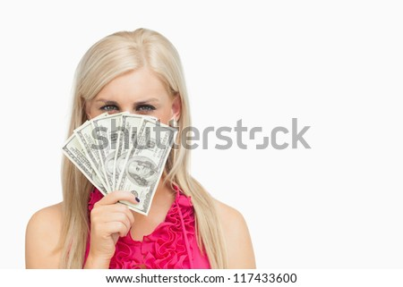 Woman hiding her face with 100 dollars banknotes against white background