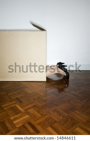woman hiding in cardboard box - stock photo