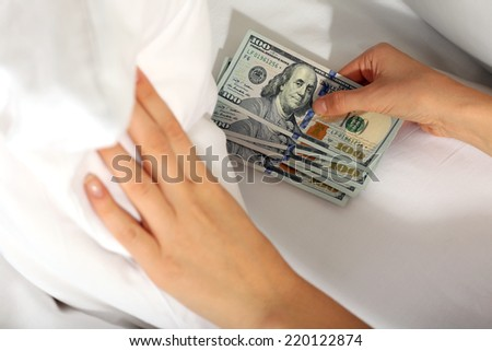 Woman hiding money under pillow at home