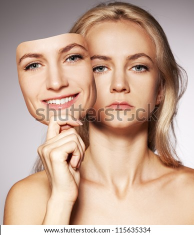 Woman hiding under the happy mask.  Hypocritical,  insincere, two-faced female - stock photo