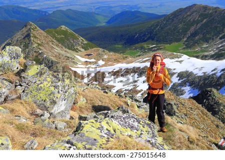 Woman hiker ascending a sunny trail on the mountain