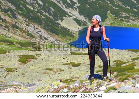 Woman hiker bathing in the sun on a mountain trail above blue lake  - stock photo