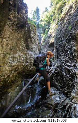 Woman hiker climbing on safety chains through a very narrow gorges - stock photo