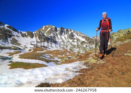 Woman hiker climbs sunny mountain stripped with snow in summer - stock photo