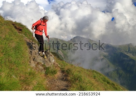 Woman hiker descending a mountain trail under white clouds - stock photo