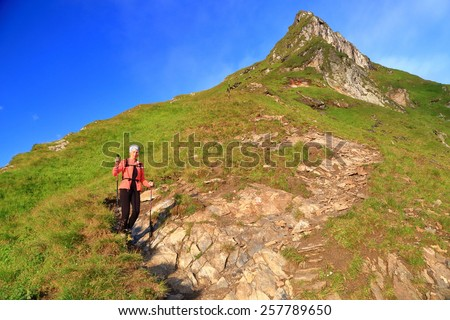 Woman hiker descending on narrow trail along sunny mountain in the morning - stock photo
